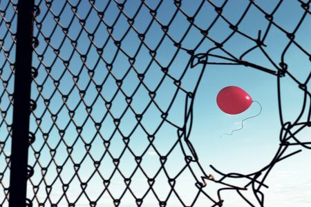 Red balloon flying in clear sky seen in hole of fence Stock Photo