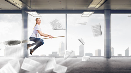 besom: Young girl in casual flying on broom in modern interior Stock Photo