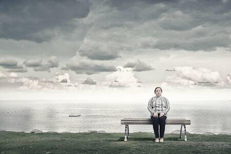 cerveza negra: Mujer robusta de mediana edad sentado en el banco