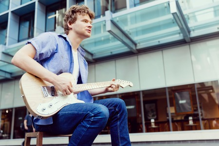 young musician: Portrait of young musician with guitar in city