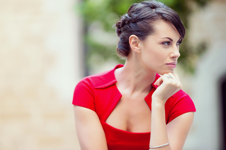 speculating: Portrait of beautiful business woman in red dress