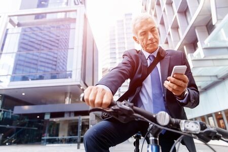 phone professional: Successful businessman in suit riding bicycle and holding mobile phone Stock Photo