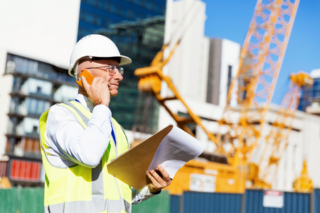 Engineer builder wearing safety vest with notepad at construction site Banco de Imagens
