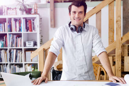 front desk: Smiling young designer standing in creative office in front of his desk