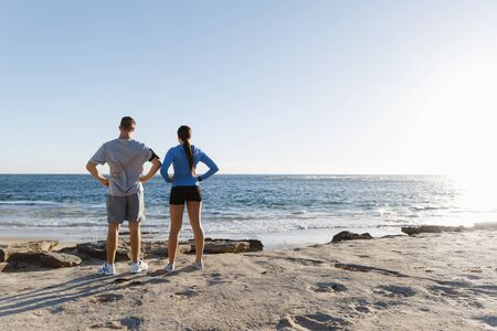 muscled: Young couple on beach training and exercising together Stock Photo