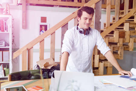 cool man: Smiling young designer standing in creative office in front of his desk