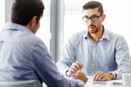 Two handsome businessman in office sitting at desk and talking