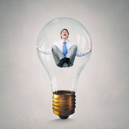 trapped: Young handsome businessman trapped inside of glass light bulb