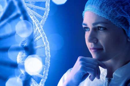 nucleotides: Woman scientist looking thoughtfully at DNA molecule image at media screen