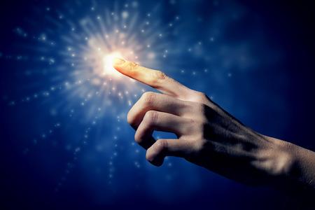insanity: Male finger touching light spot in darkness