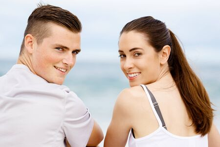 sports wear: Young couple looking at camera while sitting next to each other on beach in sports wear
