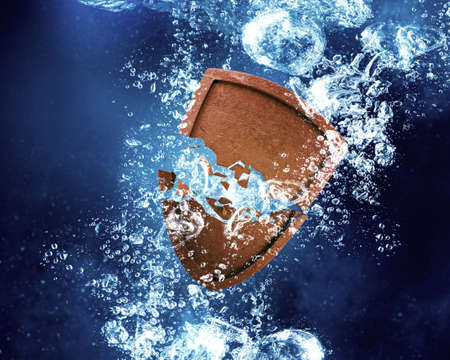 dissolving: Shield sinking and dissolving in clear blue water