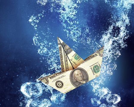 clear: Dollar banknote ship sinking in clear blue water