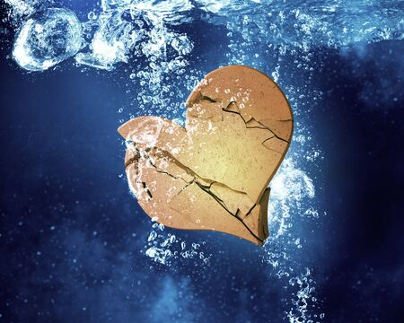 dissolving: Broken heart sinking and dissolving in clear blue water Stock Photo