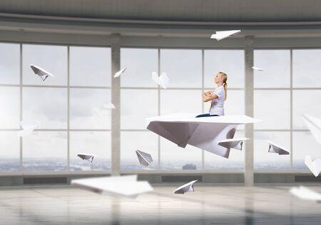 careless: Businesswoman flying paper plane in modern office interior