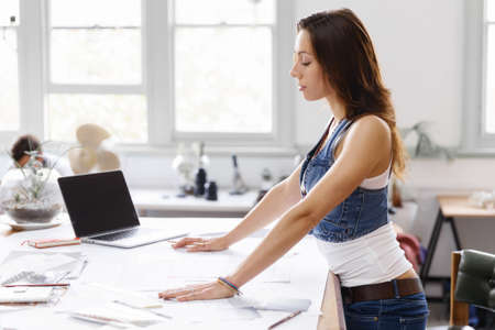front desk: Smiling young designer standing in creative office in front of her desk