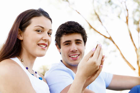 comunication: Young couple in the park with mobile phone Stock Photo