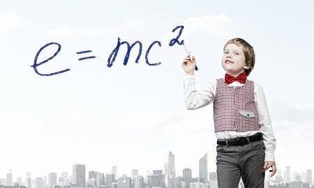 develope: Cute kid boy drawing science formula with marker on screen