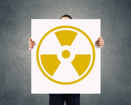 radiactividad: Empresario irreconocible que muestra la bandera con el concepto de la radiactividad