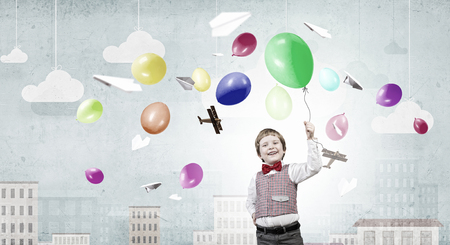 carelessness: Happy kid boy with colorful balloon in hand