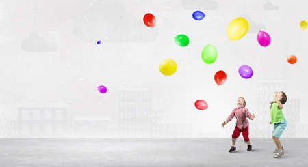 carelessness: Little cute boys playing joyfully with colorful balloon