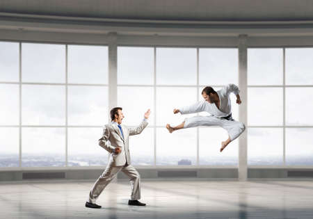 opponent: Young determined karate businessman in modern interior fighting with opponent