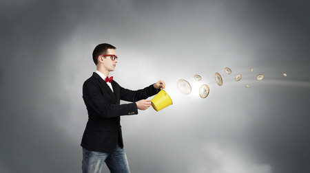 bucket of money: Young businessman holding bucket with coins flying out