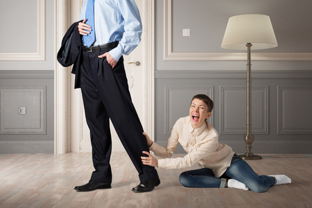 abuser: Close up of legs of man going to work and his wife asking him not to go Stock Photo
