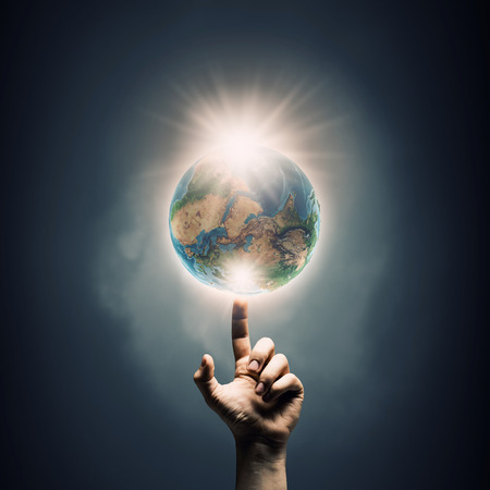 Human hand touching with finger Earth planet. Elements of this image are furnished by NASA