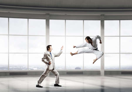 the opponent: Young determined karate businessman in modern interior fighting with opponent