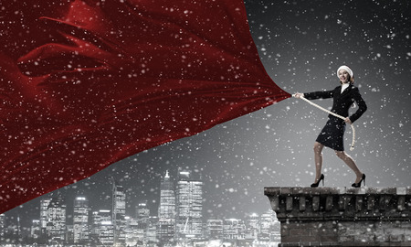 express positivity: Woman in Santa hat pulling red clothing banner. Place for text Stock Photo