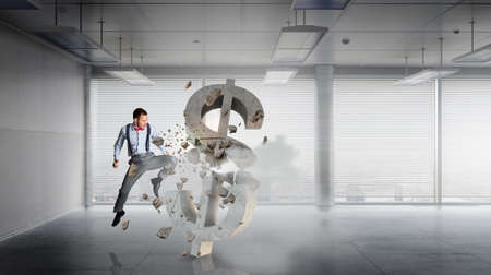 hitting: Angry businessman in modern interior hitting cracked dollar sign Stock Photo