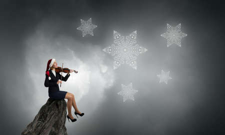 express positivity: Young businesswoman in Santa hat play violin instrument