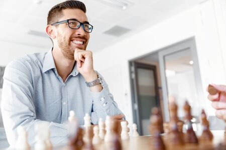 pawn adult: Young businessman playing chess in office Stock Photo