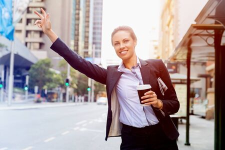 catching taxi: Portrait of young business woman catching taxi in city