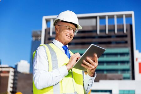 safety vest: Engineer builder wearing safety vest with notepad at construction site Stock Photo