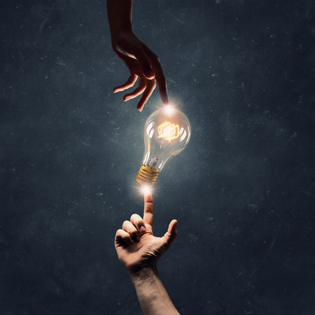 Male hand touching glowing idea light bulb