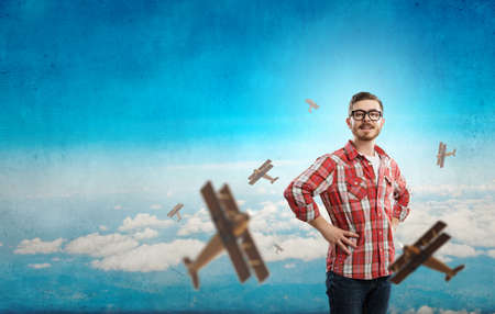 flying man: Young handsome man in checked shirt and airplanes flying around