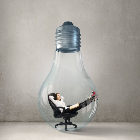 trapped: Young businesswoman trapped inside glass light bulb Stock Photo