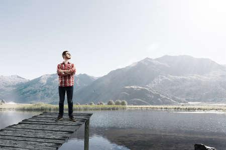 berth: Young man in casual standing on lake berth