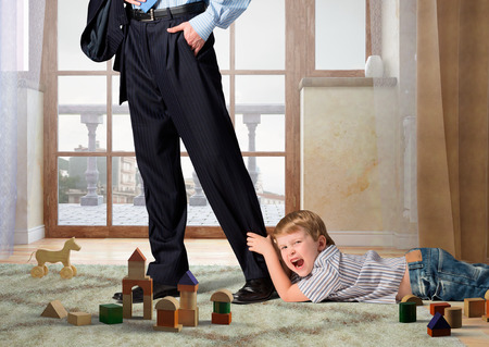 Close up of legs of man going to work and his son asking him not to go