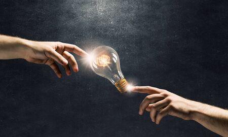 Male hand touching glowing idea light bulb