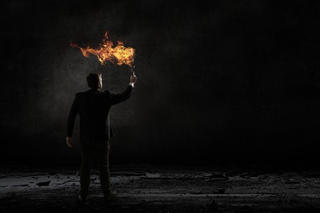 Young businessman in darkness holding burning torch in hand Stock Photo
