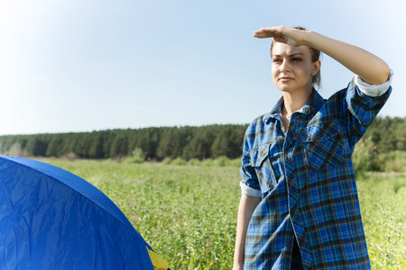 far away look: Woman standing near tent and looking into the distance