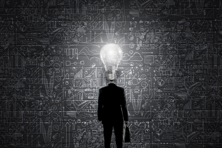 Unrecognizable businessman with glowing light bulb instead of head and sketches at background