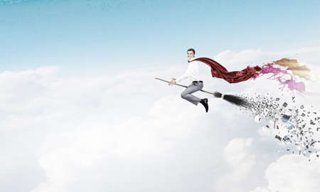 besom: Young businessman wearing cape flying on broom high in sky