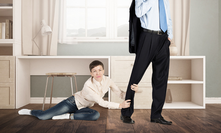 stay home work: Close up of legs of man going to work and his wife asking him not to go Stock Photo