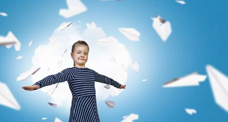 imagines: Little girl with hands spread imagines that she flies Stock Photo