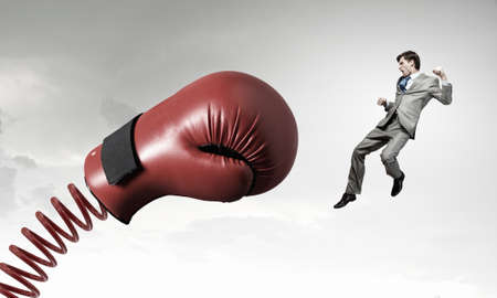 beat the competition: Young determined businessman fighting boxing glove on spring