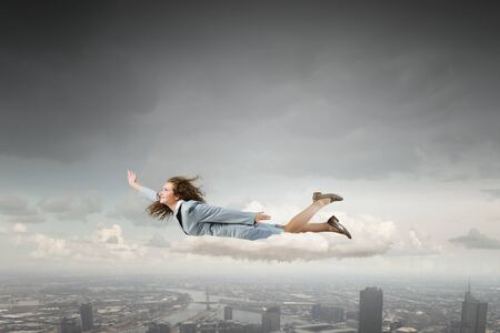 businesswoman suit: Young businesswoman in suit flying high in sky Stock Photo